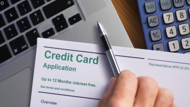 ペンはクレジットカードの申込書を机の上に置きます。 - 金利点の映像素材/bロール