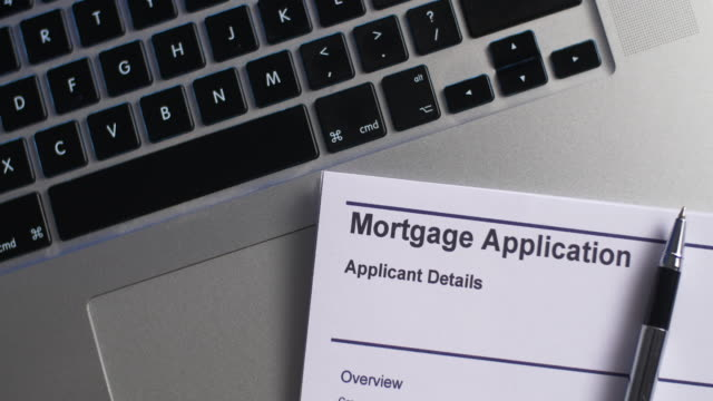 pen placed with mortgage application form on desk. - home ownership stock videos & royalty-free footage