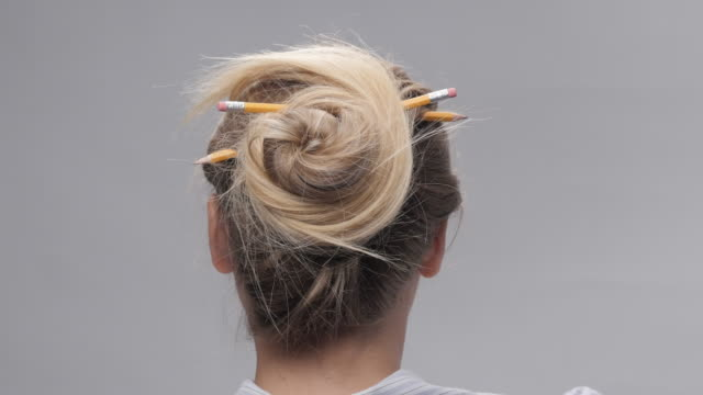pencil bun hairstyle. young woman let her hair down. spring break - hair bun stock videos and b-roll footage