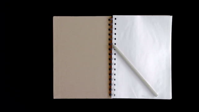 pencil on the book with blank pages,dolly shot - folded paper stock videos and b-roll footage