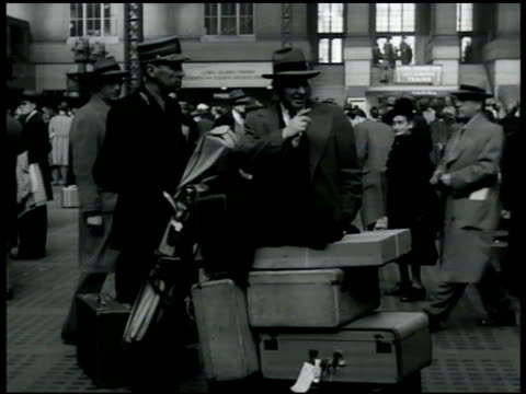 stockvideo's en b-roll-footage met penn station vs travelers man w/ porter male lighting cigarette w/ woman sitting on luggage 'the st louisan' train sign people moving in line for... - 1949
