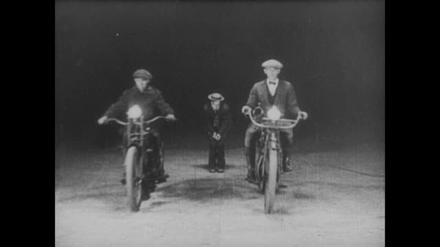 1921 a penniless man (buster keaton) attempts to commit suicide by jumping in front of what looks like a car, but the headlights belong to two motorcycles and the pass by on either side of him - hosentasche stock-videos und b-roll-filmmaterial