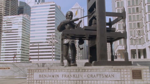 pennsylvania office buildings loom over a statue of benjamin franklin working at a printing press. - benjamin franklin stock videos & royalty-free footage