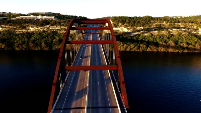 pennybacker bridge or 360 bridge or capital of texas highway bridge at sunset on the colorado river or town lake spring time aerial flying directly over the top of the bridge - austin texas stock videos & royalty-free footage