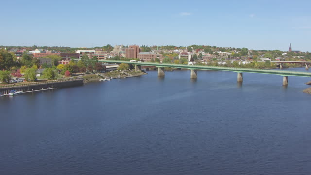 WS AERIAL POV Penobscot River and downtown Bangor, vehicles moving on bridge / Bangor, Maine, United States
