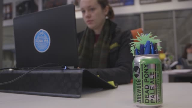 Pens sit in a Brewdogbranded can as an employee works on a laptop computer at a desk in the Brewdog Plc brewery and headquarters in this arranged...