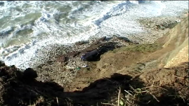 pensioner survives after driving over 100 foot cliff england isle of wight ext high angle view of smashed car at bottom of cliffs rescue worker... - isle of wight stock videos & royalty-free footage