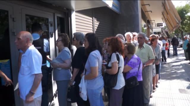 vidéos et rushes de pensioners without atm cards wait in queue outside a bank branch to withdraw money from their pension funds on july 02, 2015 in athens, greece. a... - file attente