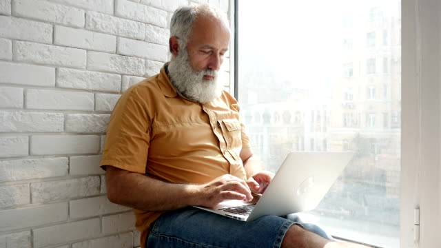 Pensive bearded man working on laptop while sitting on the window-sill