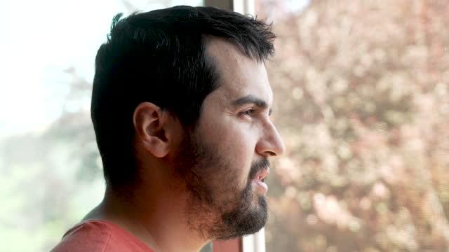 eftertänksam skäggig ung man tittar genom ett fönster - profil sedd från sidan bildbanksvideor och videomaterial från bakom kulisserna