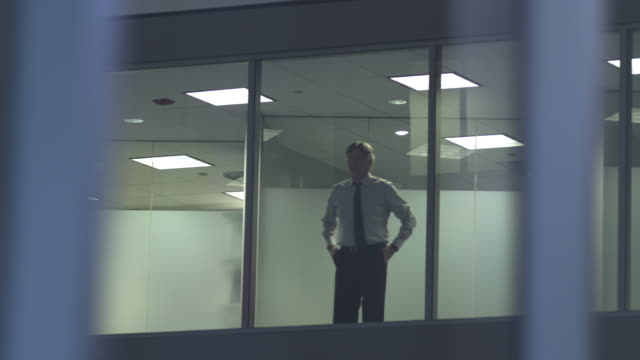 WS PAN Pensive businessman looking through window in office corridor, Chicago, Illinois, USA