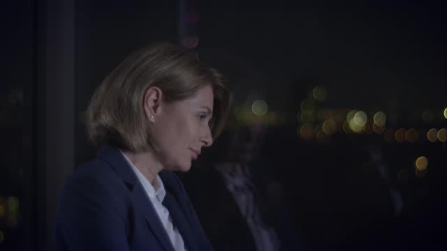 Pensive businesswoman standing in front of window