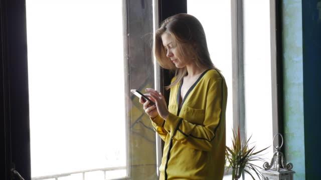Nachdenklich Mädchen Mitteilung per Telefon zu schreiben, während Sie auf dem Fenster lehnen