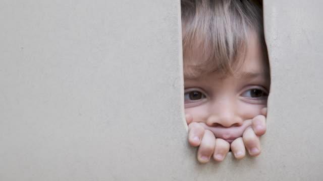 pensive little boy peeking through a hole - peeking stock videos & royalty-free footage