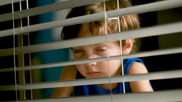 pensive little boy peeking through a window at night - film moving image stock videos & royalty-free footage