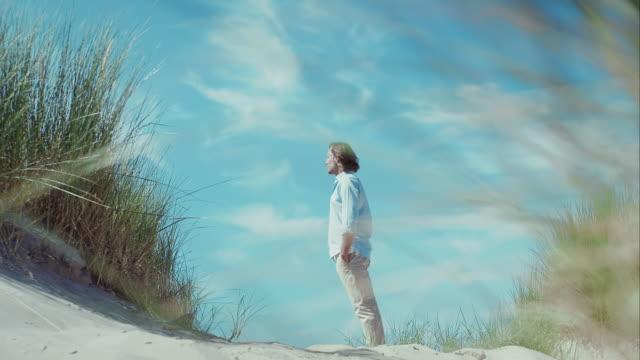 Nadenkend man op strand op zoek naar afstand