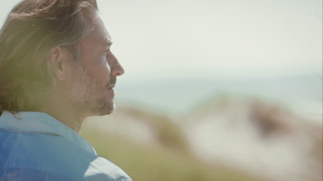 pensive man at beach looking into distance - distant stock videos and b-roll footage