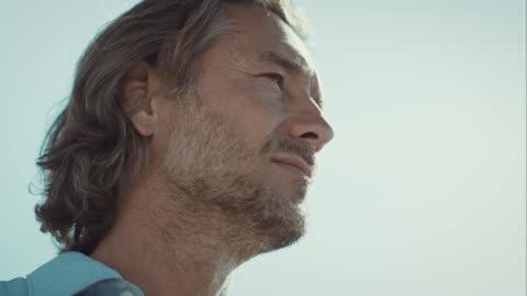 nachdenklicher mann am strand, blick von unten in gehminuten - männer stock-videos und b-roll-filmmaterial