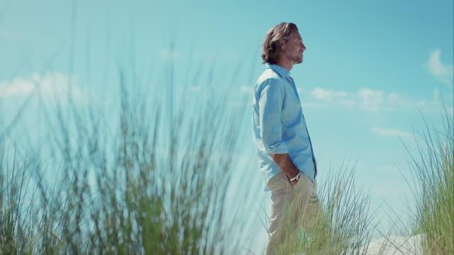 vídeos de stock, filmes e b-roll de homem pensativo na praia, olhando para a distância - distante