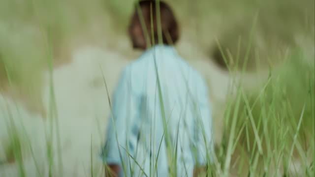 Pensive man at beach walking through dunes