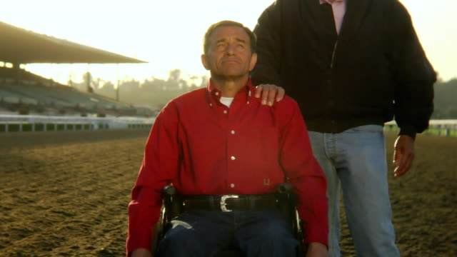 CU, TU, Pensive mature man on wheelchair on horse race track, other man resting hand on his shoulder, California, USA