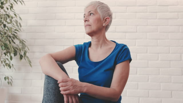 Pensive mature woman relaxing at home and day dreaming.