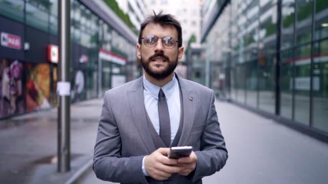 vidéos et rushes de homme d'affaires moderne pensif pensant à l'information de travail qu'il a reçue sur le téléphone mobile - se mordre les lèvres
