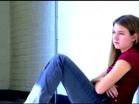vídeos y material grabado en eventos de stock de pensive teenage girl in school hallway - sólo una adolescente