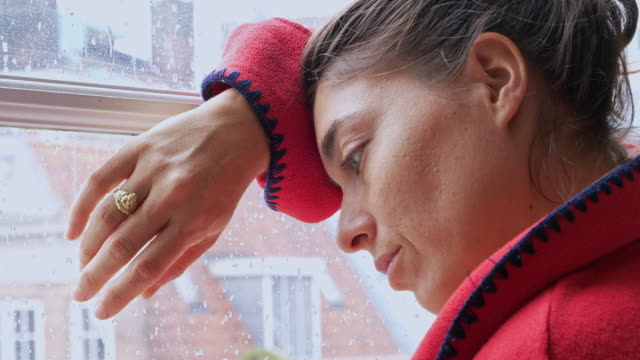 pensive woman by window on rainy day - depression sadness stock videos & royalty-free footage
