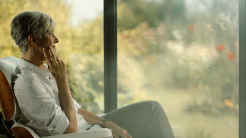 pensive woman sitting in her living room - sitting stock videos & royalty-free footage