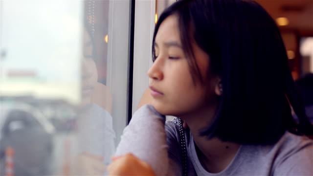 窓を通して見る物思いにふける少女 - 景色を眺める点の映像素材/bロール
