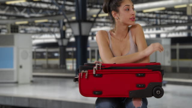 pensive young latin woman waits with suitcase at subway station - bagaglio video stock e b–roll
