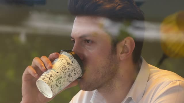 4k: pensive young man in the coffee shop - disposable cup stock videos and b-roll footage