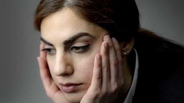 物思いにふける若い女性。頭手に傾いています。目が離れています。灰色の背景。 - 横顔点の映像素材/bロール