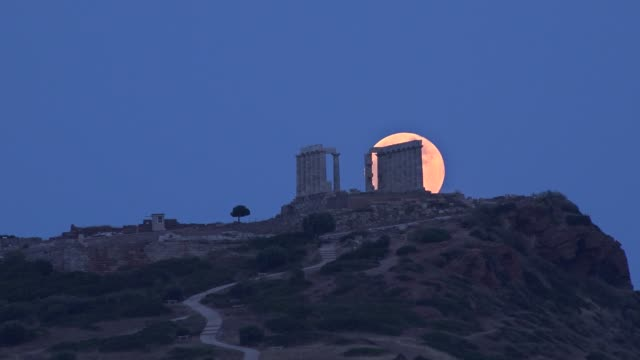 penumbral eclipsed strawberry moon is rising above the ancient temple of poseidon in cape sounion southeast of athens greece on june 5 2020 - athens greece video stock e b–roll