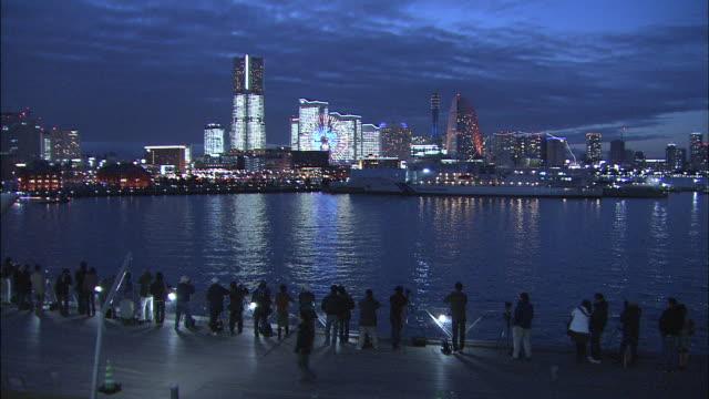 People admire the lights of the Minato Mirai in Yokohama, Japan.