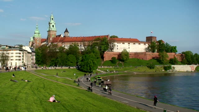people along the bank of visla river, wawel castle is in the background. poland, krakow - circa 13th century stock videos and b-roll footage