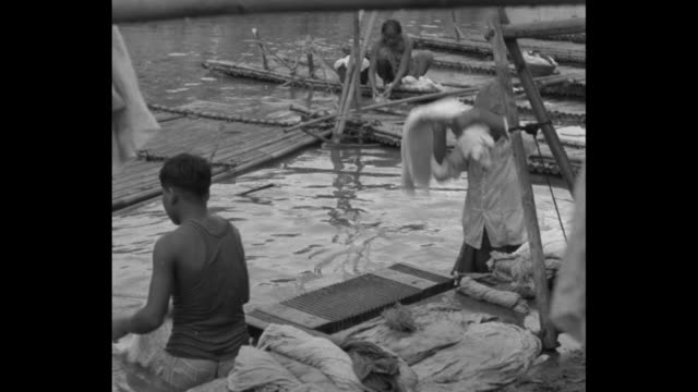 LS people along the riverbank wash clothes boys wrestle on raft people walk carts and motor vehicles pass in background / MLS same / MCU men in river...