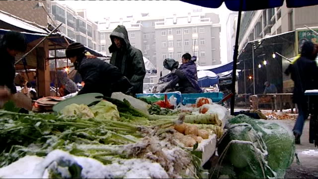 people along through snow and ice covered city of hangzhou; woman working on market stall / vegetables being sold / people shopping at vegetable... - hangzhou stock videos & royalty-free footage
