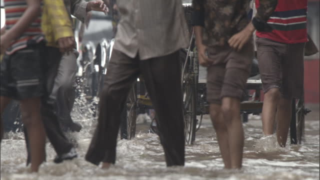 people and bikes on flooded road, varanasi available in hd. - walking in water stock videos & royalty-free footage