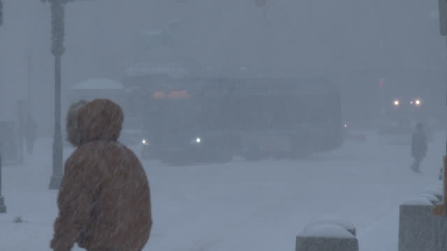 People and cars are barely visible as heavy snow and strong winds create near whiteout conditions during an intense blizzard in Connecticut