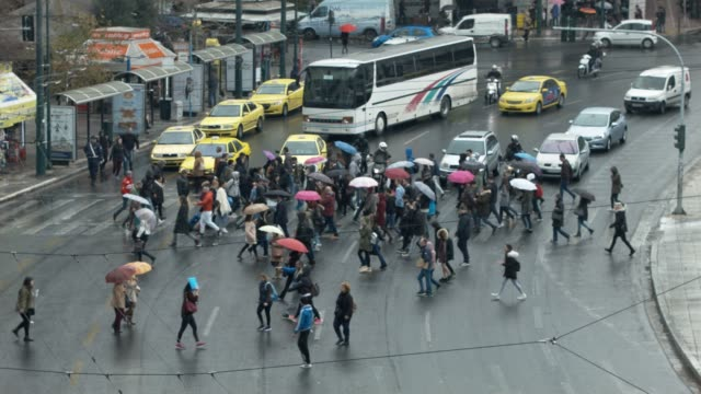 People and cars at traffic lights and crosswalk downtown Athens, Greece, during rain at Syntagma Square