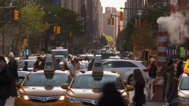 People and cars fill busy New York City street and move about in slow motion.