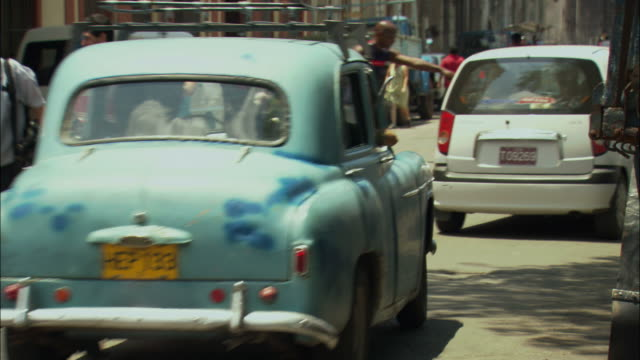 MS, TU, people and  cars on street outside tobacco factory, Cuba