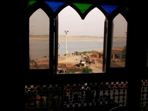 ha, ws, people and cattle at river ganges seen through ornate window, varanasi, india - medium group of animals stock videos & royalty-free footage
