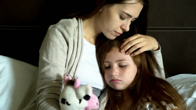 vídeos de stock e filmes b-roll de people and family concept - sad girl with mother sitting on sofa at home.single mom worries about her future.girl missing her father. - mágoa atormentado