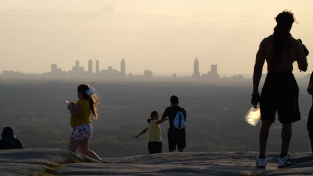 people and family enjoying atlanta skyline from stone mountain summit at sunset - skyline stock videos & royalty-free footage