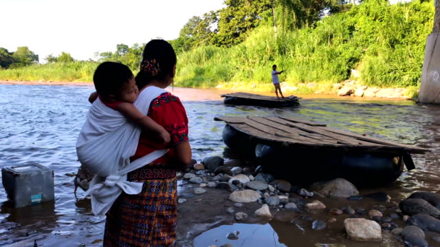 people and goods cross the suchiate river from guatemala into mexico on august 9, 2018 in talisman, mexico. the illegal crossing point is located... - chiapas stock-videos und b-roll-filmmaterial