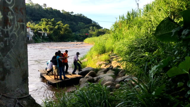 People and goods cross the Suchiate River from Guatemala into Mexico on August 9 2018 in Talisman Mexico The illegal crossing point is located just...