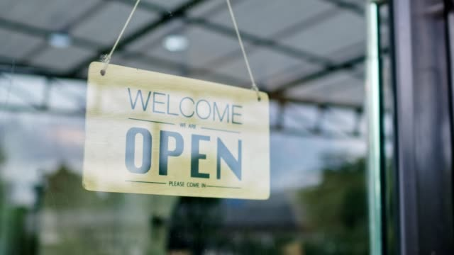 people and service concept,small business. asian man wear a mask hanging banner with open word on door or window for open shop and ready to service,available - open sign stock videos & royalty-free footage